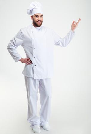 the welcome: Retrato de cuerpo entero de un cocinero feliz cocinero que muestra gesto de bienvenida aislado en un fondo blanco Foto de archivo