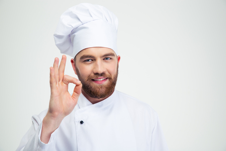 Portrait of a smiling male chef cook showing ok sign isolated on a white background