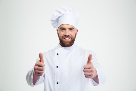 Portrait of a happy male chef cook showing thumbs up isolated on a white background