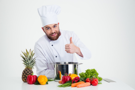 Portrait of a happy male chef cook preparing food and showing thumb up isolated on a white background