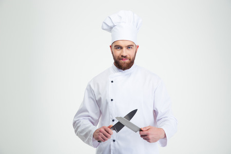 Portrait of a happy male chef cook sharpening knife isolated on a white background Foto de archivo