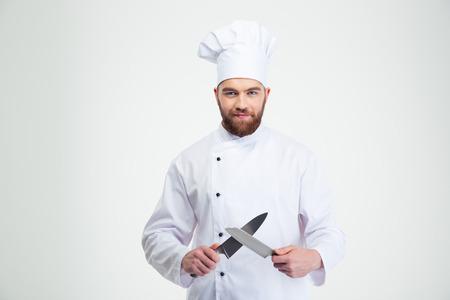 cuchillo de cocina: Retrato de un cocinero feliz Cocinero de sexo masculino que afila el cuchillo aislado en un fondo blanco Foto de archivo