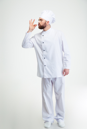 white beard: Full length portrait of a male chef cook making tasty gesture by kissing fingers isolated on white Stock Photo