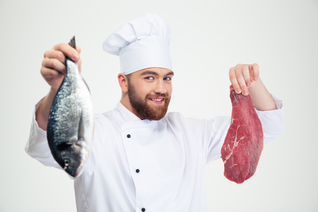 teethy: Portrait of a smiling male chef cook holding fresh fish and meat isolated on a white background