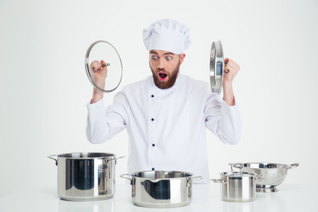 Portrait of a funny male chef cook sitting at the table with dishes isolated on a white background