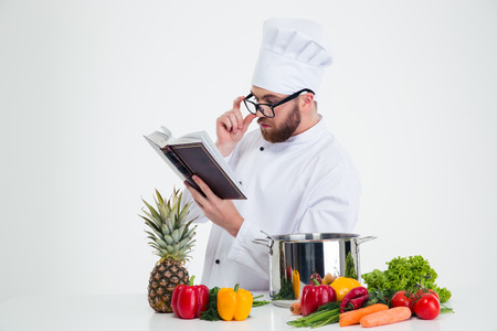recipe book: Portrait of a male chef cook in glasses reading recipe book isolated on a white background