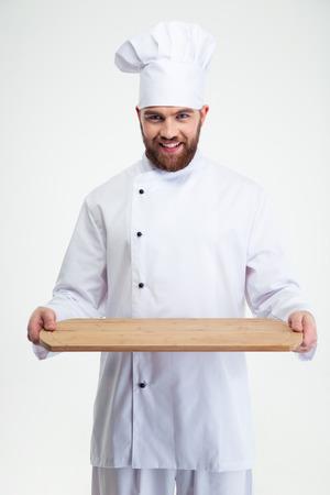 Portrait d'un homme heureux chef cuisinier tenant planche en bois isolé sur un fond blanc