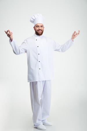 panadero: Retrato de cuerpo entero de un cocinero sonriente cocinero que muestra gesto de bienvenida aislado en un fondo blanco