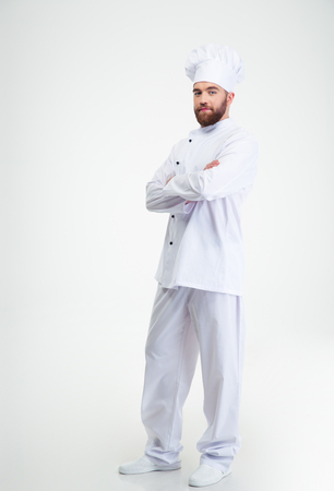 Full length portrait of a happy male chef cook standing with crossed hands isolated on a white background Stock Photo