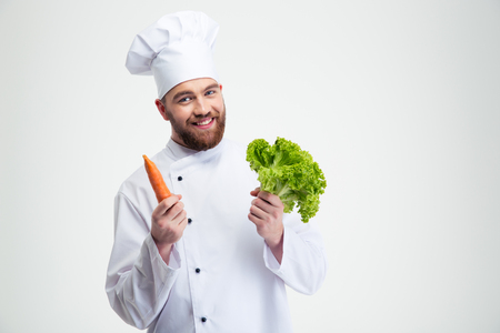 Portrait of a smiling chef cook holding salad and carrot isolated on a white background Imagens