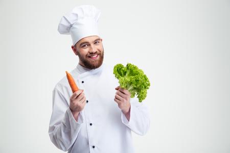cocinero: Retrato de un cocinero sonriente cocinero sostiene la ensalada y zanahoria aislado en un fondo blanco Foto de archivo