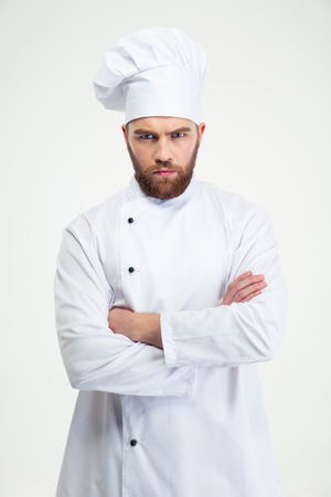 grouchy: Portrait of angry male chef cook standing with arms folded isolated on a white background Stock Photo
