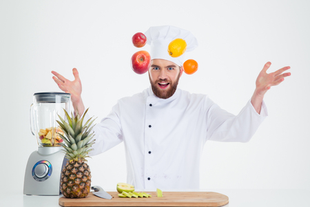 hapy: Portrait of a hapy male chef cook juggle with fruits isolated on a white background Stock Photo