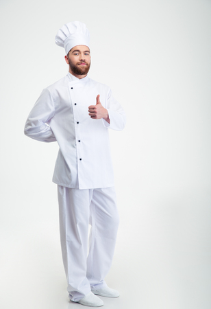 Full length portrait of a handsome male chef cook showing thumb up sign isolated on a white background Foto de archivo