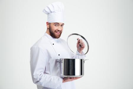 Retrato de un cocinero de sexo masculino sonriente cocinero que sostiene la cacerola aislado en un fondo blanco