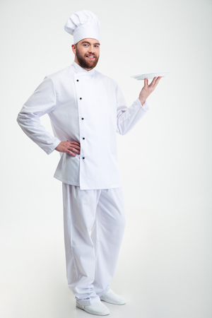 cook: Portrait of a happy male chef cook standing with plate isolated on a white backgorund