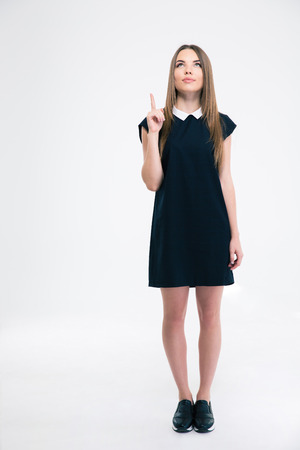 19's: Full length portrait of a thoughtful woman pointing finger up at copyspace isolated on a white background