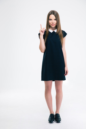 19's: Portrait of a happy young woman pointing finger up at copyspace isolated on a white background. Looking at camera