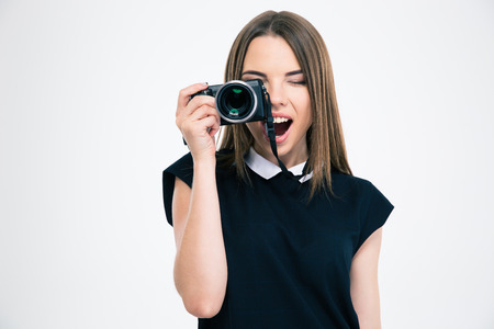 camera: Portrait of a cheerful woman making photo on camera isolated on a white background Stock Photo