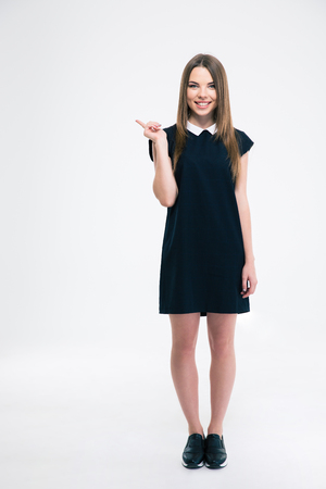 19's: Full length portrait of a smiling woman pointing finger away isolated on a white background