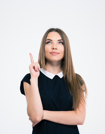 19's: Portrait of a pretty thoughtful woman pointing finger up at copyspace isolated on a white background