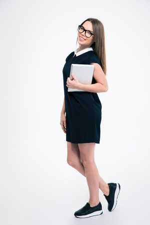 person standing: Full length portrait of a smiling young woman standing with tablet computer isolated on a white background