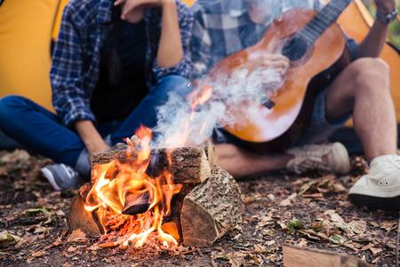 campamento: Retrato Closeu de una pareja sentada con la guitarra cerca de la hoguera en el bosque Foto de archivo
