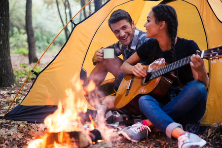 camps: Portrait of a young couple sitting with guitar near bonfire in the forest