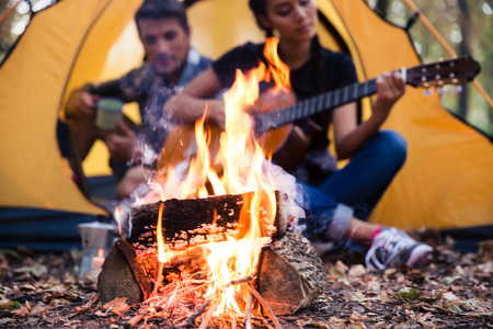 fall trees: Portrait of a young couple sitting with guitar near bonfire in the forest