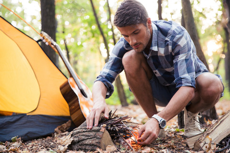 kindling: Portrait of a handsome man kindle bonfire in the forest Stock Photo