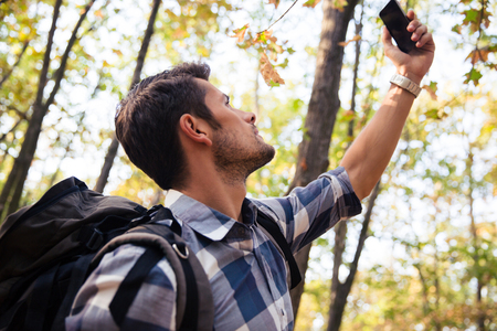 caching: Portrait of a man searching connection on the phone in the forest Stock Photo