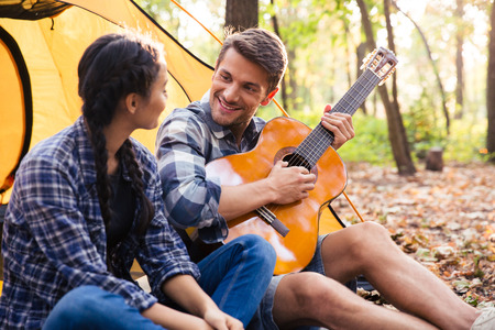 guy playing guitar: Portrait of a happy couple sitting with guitar in the forest