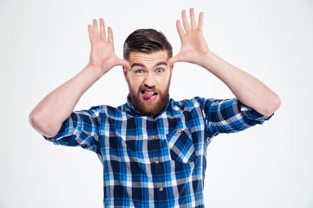 imitating: Portrait of a young man showing big ears with his hands and tongue isolated on a white background