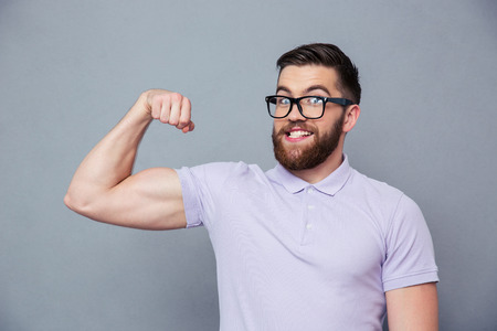 Portrait of a funny man in glasses showing his muscles over gray background