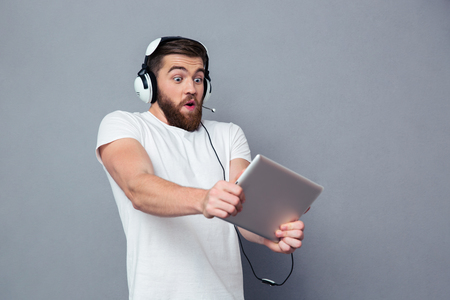 excited: Portrait of a young man playing on the tablet computer with headphones over gray background