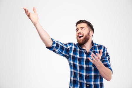 cantando: Retrato de un hombre de canto casual y haciendo un gesto con las manos aisladas en un fondo blanco