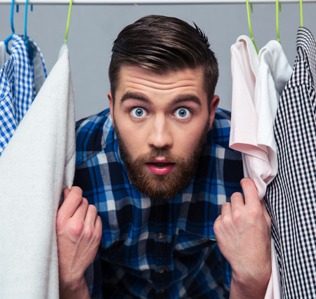 staring at the camera man: Portrait of a surprised hipster man standind near rack with clothes and looking at camera Stock Photo