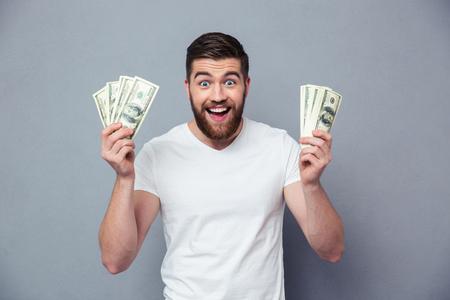 pieniądze: Portret wesołej człowiek gospodarstwa banknotów dolarowych na szarym tle