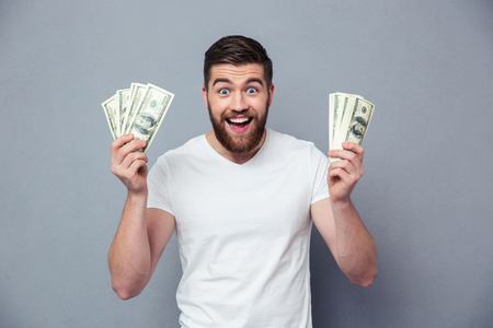 dinero: Retrato de un hombre con alegres billetes de un dólar sobre fondo gris
