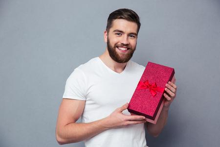 灰色の背景の上のギフト ボックスを押し、カメラを見て笑みを浮かべてカジュアルな男の肖像 写真素材