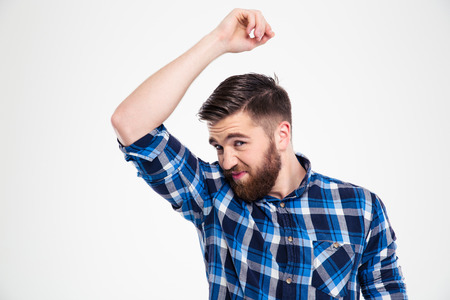 unbearable: Portrait of a casual man smelling his armpit isolated on a white background Stock Photo