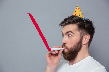 party hat: Portrait of a young man with party hat blowing in whistle over gray background