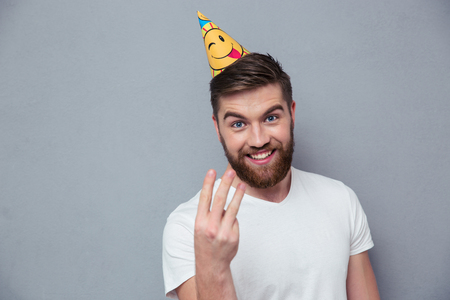 three fingers: Portrait of a smiling man with birthday hat showing three fingers over gray background