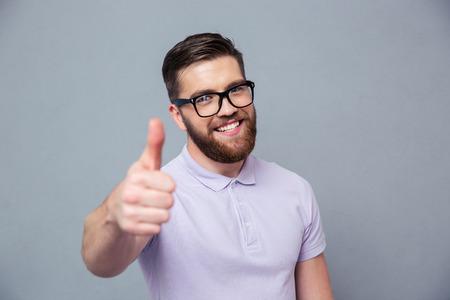 Portret van een lachende man in een bril blijkt duim omhoog over grijze achtergrond