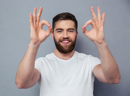 ok sign: Portrait of a happy casual man showing ok sign with fingers over gray background
