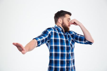 stench: Portrait of a casual man covering his nose and showing stop gesture with palm isolated on a white background