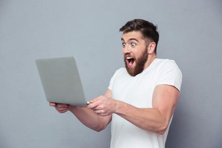 relajado: Retrato de un hombre alegre que usa el ordenador portátil sobre fondo gris Foto de archivo