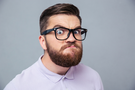funny glasses: Portrait of a funny hipster man looking at camera over gray background Stock Photo