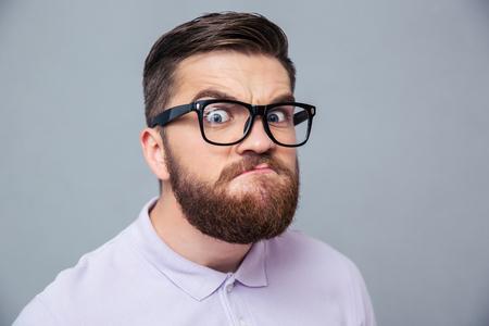 caras graciosas: Retrato de un hombre divertido inconformista mirando a la cámara sobre fondo gris Foto de archivo
