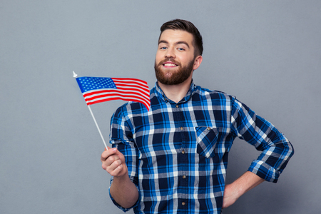 4s: Portrait of a smiling man holding USA flag over gray background Stock Photo